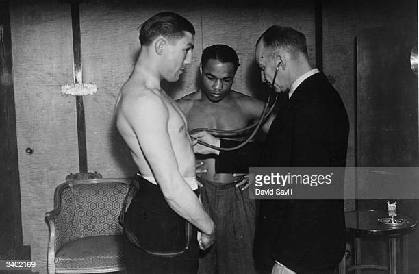 A doctor listens to Liverpool middleweight boxer Ernie Roderick's heart while his opponent Hurrican Henry Armstrong looks on He lost on a points...