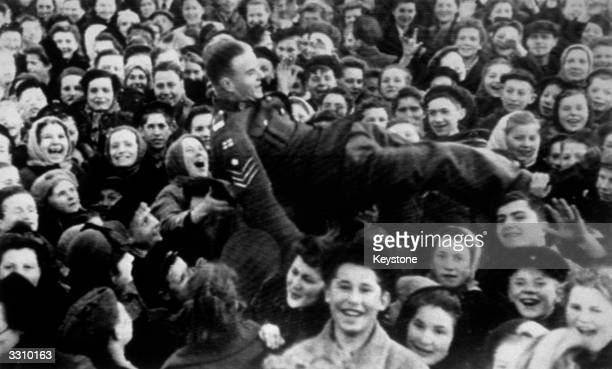 A British sergeant is lifted up as Moscow women celebrate VE Day