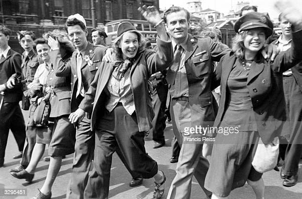 A happy group marches down a London street on VE Day Original Publication Picture Post 1991 This Was VE Day In London pub 1945