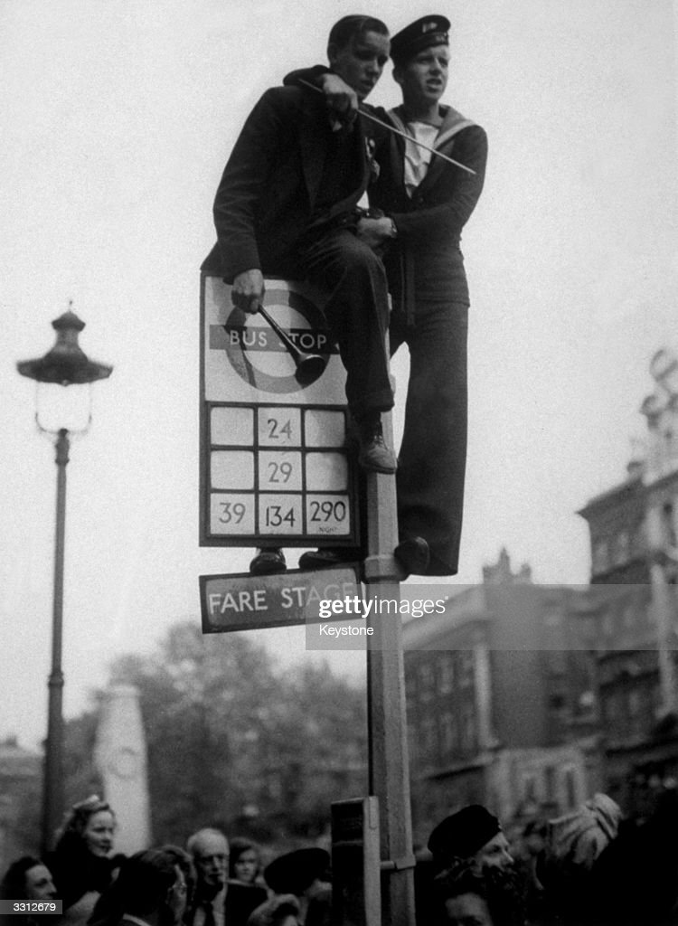 A sailor and a civilian clamber on top of a bus stop in Whitehall, London, during the VE Day celebrations.