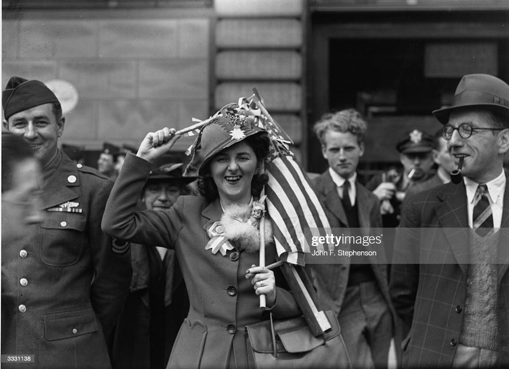 A woman holding an American flag over her head during VE day celebrations in Piccadilly Circus, London.