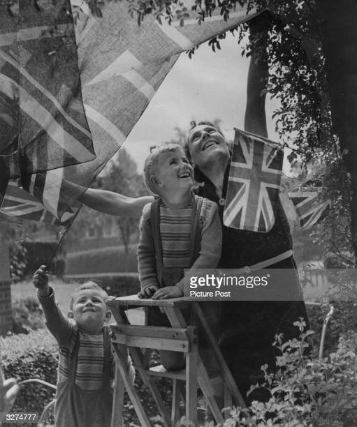 Children help to put up bunting and flags for the VE Day celebrations Original Publication Picture Post 1991 This Was VE Day In London pub 19th May...