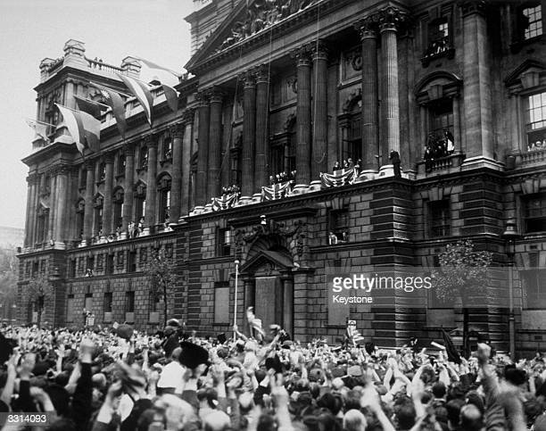 Crowds cheering Churchill as he appeared on the balcony of the Ministry of Health in Whitehall, and made an official announcement that the war in...