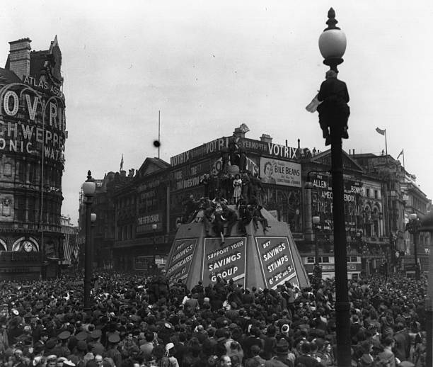 Crowds in Piccadilly Circus climb lampposts and the...