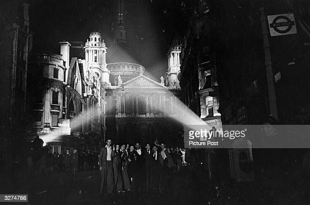 Floodlights illumunate the building tops near St Paul's as revellers celebrate the German surrender in the dark streets of London on VE Night...