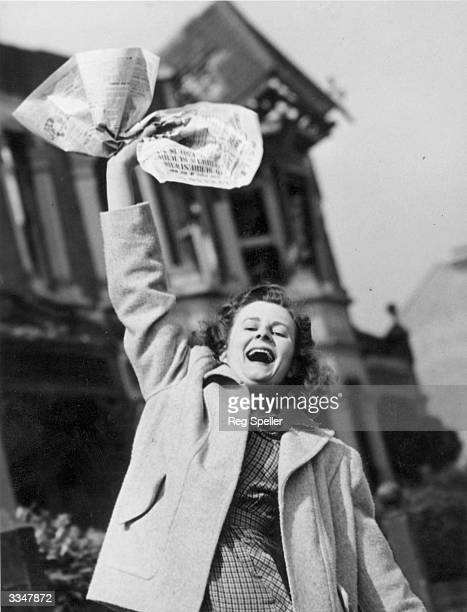 Mrs Pat Burgess of Palmers Green North London waves a newspaper containing the news of Germany's surrender in World War II She hopes this means that...