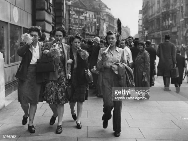 VE Day revellers blowing party trumpets in Piccadilly London