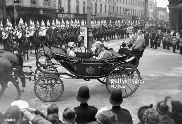 Princess Elizabeth and Princess Margaret travel in an open coach with Queen Ingrid of Denmark as they proceed between Victoria Station and Buckingham...