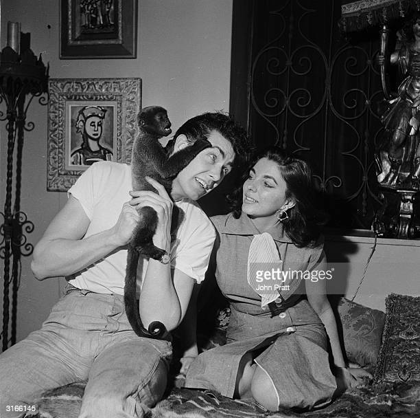 British starlet Joan Collins with her husband Maxwell Reed and their pet monkey Spider at their Spanishthemed home in London's Mayfair