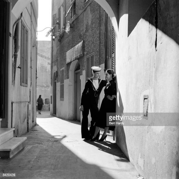 A British Navy sailor talking to a local girl on a narrow street in Gibraltar Original Publication Picture Post 7154 Why We Must Keep Gibraltar pub...