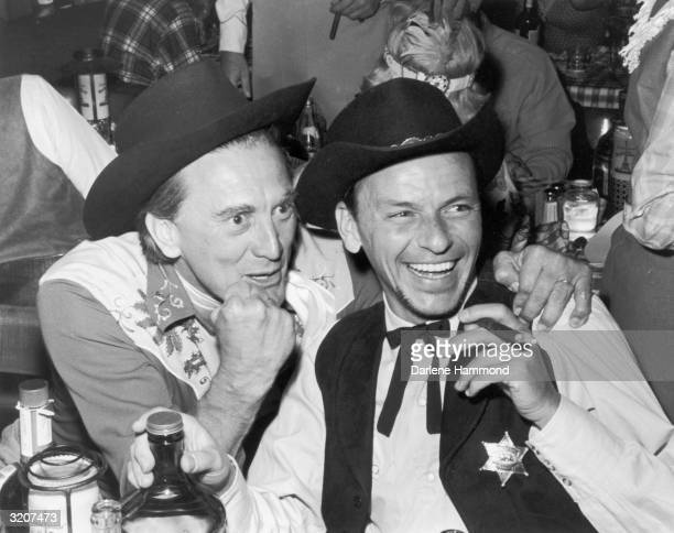 American actors Kirk Douglas and Frank Sinatra, dressed in Western-inspired costumes, laugh together at a share party at the Moulin Rouge, Paris,...