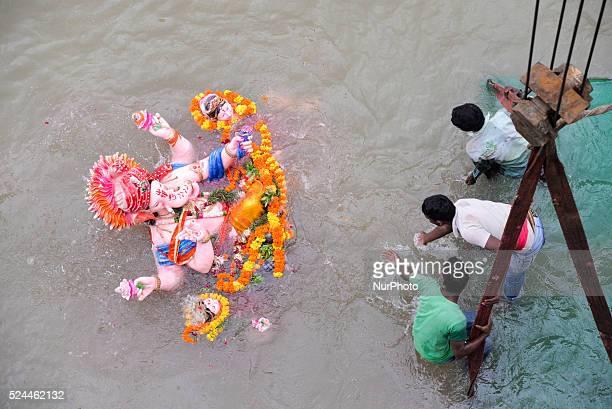 AHMEDABAD GUJARAT/ INDIA 8th MONDAY SEPTEMBER 2014 Devotees carry an idol of the Hindu god Ganesh the deity of prosperity into the Sabarmati river...