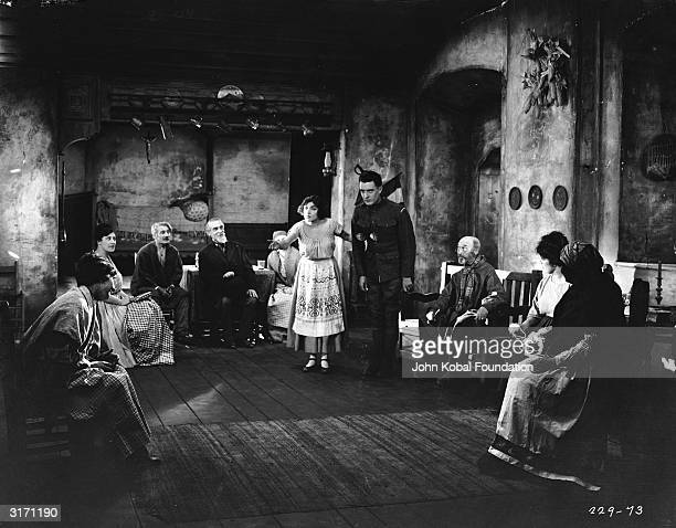 Local French girl Renee Adoree introduces American soldier John Gilbert to a roomful of elderly folk in the World War I drama 'The Big Parade'...