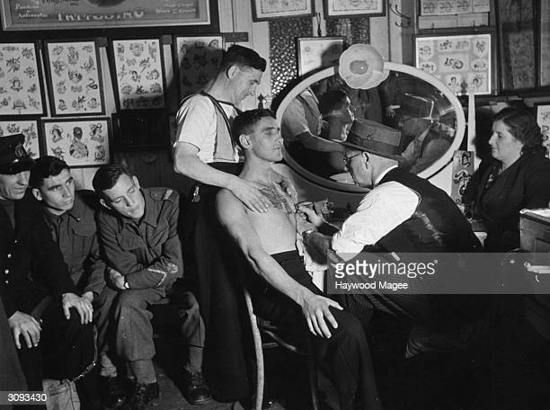 Leading tattooist Professor Cecil Rhodes of Dover completes a twohour job on Seaman Collins whose shipmate grips him by the shoulders for support...