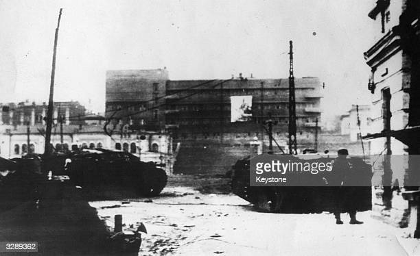 Nazi tanks stand in the foreground of the battered city of Kharkov captured in October industrial centre of the Donetz Basin A poster asking for...