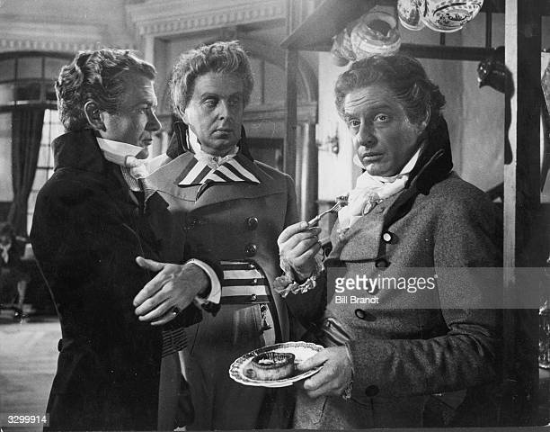 Robert Morley and John Mills William Wilberforce and Fox respectively talk to Robert Donat as Pitt while he eats a snack A scene from 'Young Mr Pitt'...