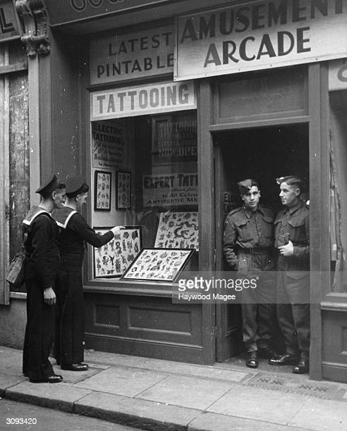 Seaman Sydney Collins and his shipmate inspect the decorations on offer at Professor Cecil Rhodes' Dover tattoo parlour Original Publication Picture...