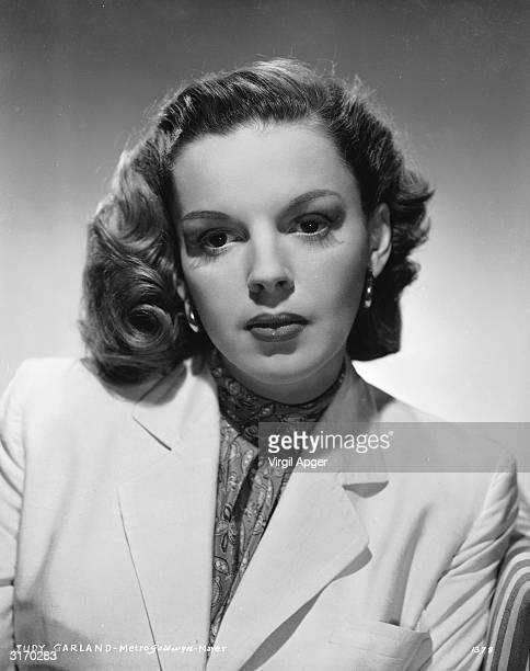Wearing her hair swept to one side and looking demure in a suit and high necked blouse film star Judy Garland