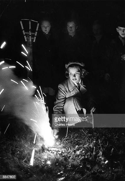 A girl lights a firework at a Guy Fawkes night party Original Publication Picture Post 6202 OOOH pub1952