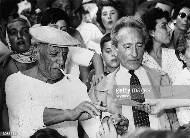 Spanish painter sculptor printmaker designer and ceramicist Pablo Picasso at a bullfight near Cannes with French poet and film director Jean Cocteau