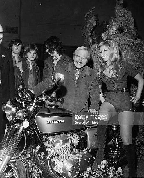 British comedian Dick Emery poses with Anita Paul and a Honda motorbike at the International Motorcycle and Cycle Show in Earls Court London