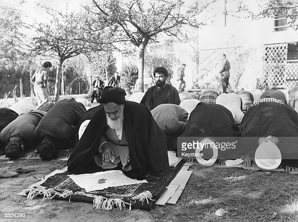 Iranian religious and political leader the Ayatollah Khomeini at prayer with his followers in his residence outside Paris.