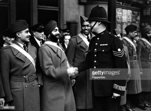 8th October 1940 A bearded and turbaned Indian pilot receives a handshake of welcome from a railway police sergeant on his arrival in London prior to...