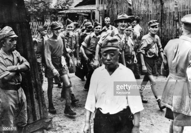 Japanese soldiers turn away as British and Australian soldiers stream out of their prison camp on Formosa after liberation by US marines Some of them...