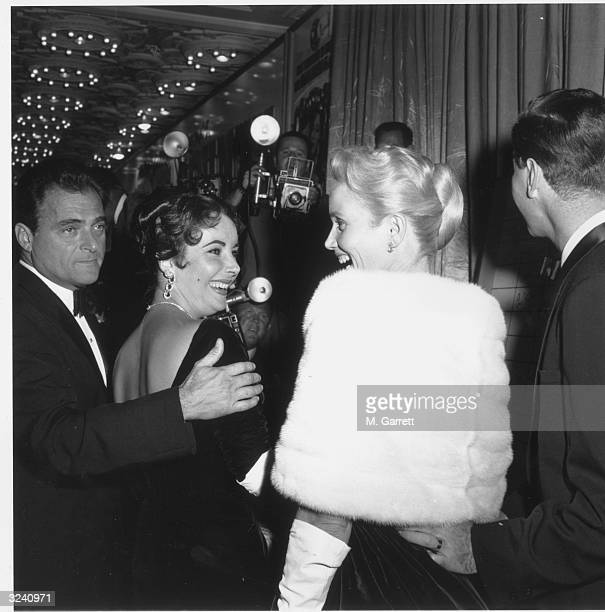 American producer Mike Todd watches as his wife, British-born actor Elizabeth Taylor , and American actor Eva Marie Saint face each other and laugh...