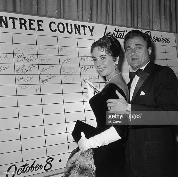 British-born actor Elizabeth Taylor smiles with her third husband, film producer Mike Todd, as she signs the guest board at the premiere of director...