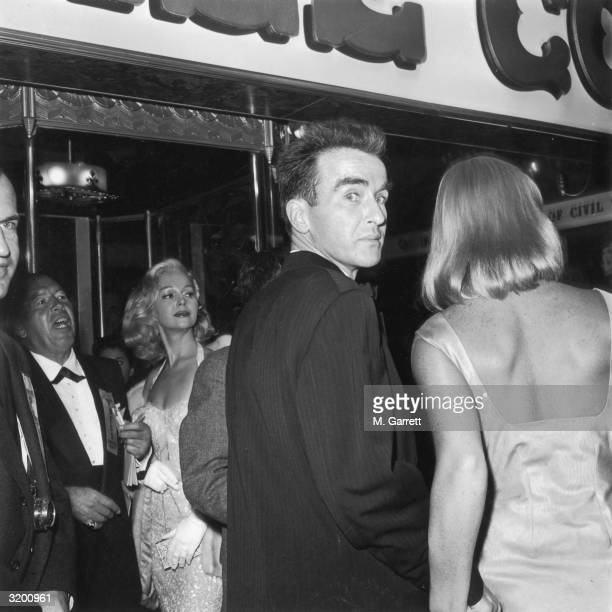 View from behind of American actor Montgomery Clift, looking over his shoulder, and Swedish actor May Britt, at the premiere of Canadian director...