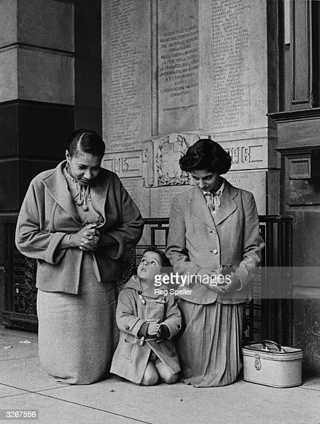 Outside the Italian Roman Catholic Church in Clerkenwell, two women and a child kneel in prayer for Pope Pius XII, as they wait for the commencement...