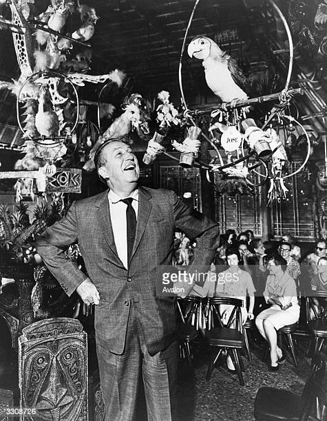 Cartoonist Walt Disney admires one of his electronicallycontrolled animated birds at the opening of his latest character show at Disneyland California