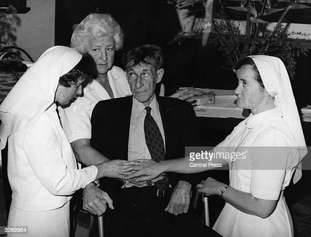 English faith healer Mrs Mary Rodgers places her hand on a patient with a slipped disc during one of her faith healing sessions at St John of God...