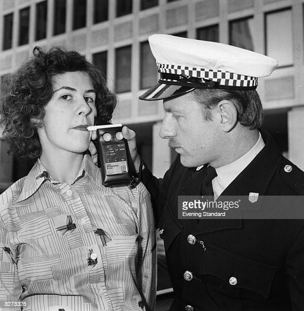 A policeman carrying out a breathalyser test on a young woman outside the Home Office
