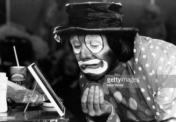 David Oliver Craik touches up his makeup for his persona Mr Bosco at the Clown Cavalcade