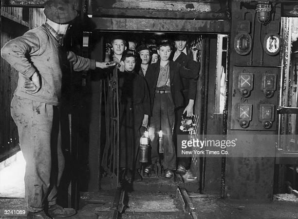 Boy miners known as 'Bevin Boys' crowd into a shaft as they wait to descend into the coal mine Markham Colliery Yorkshire England