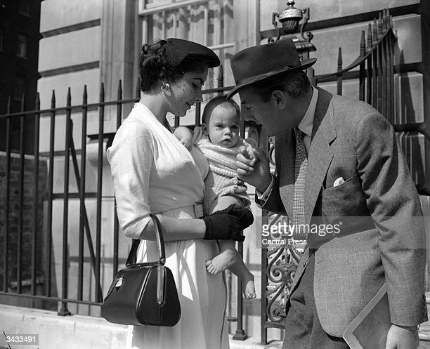 Film star couple Michael Wilding and Elizabeth Taylor with their eightmonthold son Michael Wilding Jnr outside their apartment in London's Grosvenor...