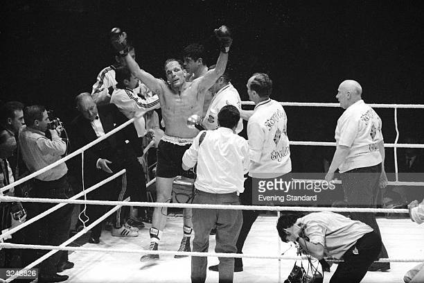 British boxer Henry Cooper raises his arms in triumph after his defeat of Karl Mildenberger to win the European Heavyweight title