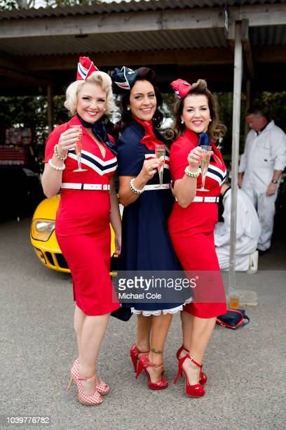 Three stylish ladies holding glasses of champagne in the Paddock area at the 20th anniversary of the Goodwood Revival at Goodwood on September 8th...