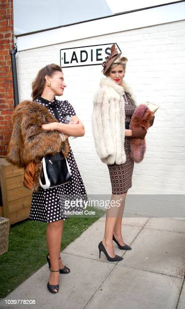 Two stylish ladies wearing fur jackets waiting outside the 'Ladies' at the 20th anniversary of the Goodwood Revival at Goodwood on September 8th 2018...
