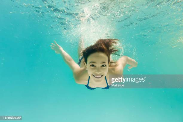 8-year-old girl happily swimming underwater - bottomless girl stock pictures, royalty-free photos & images