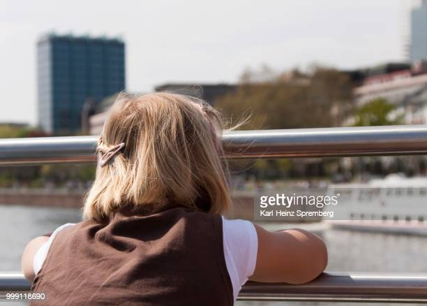 8-year-old girl looking towards Frankfurt am Main during a boating trip, Frankfurt am Main, Hesse, Germany
