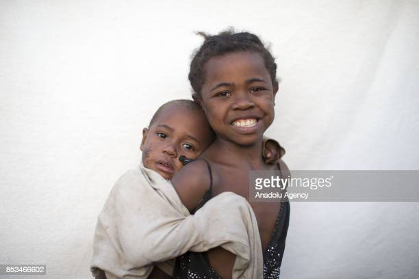 8yearold Heraina Ibonia holding her brother in her arms poses in Antananarivo Madagascar on September 24 2017 In Madagascar most of the girls with no...