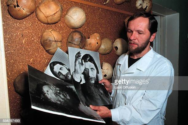 Scientist Sergei Nikitin from the Central Institute of Pathology in Moscow examines photographs of Grigori Rasputin 90s in Moscow in Russia
