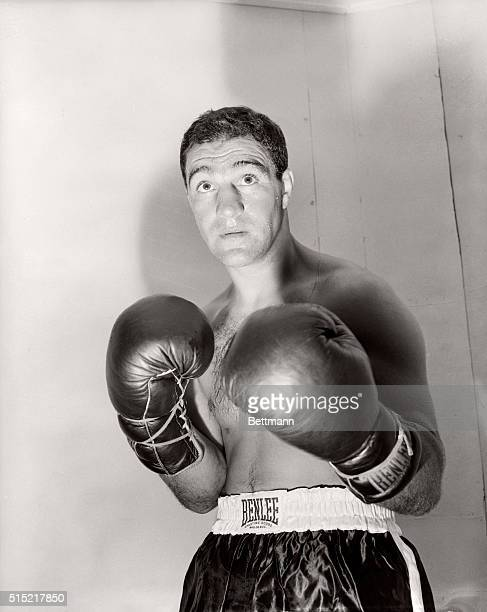 Boxer Rocky Marciano poses for a studio portrait that depicts him in a menacing fight pose, boxing gloves ready for action.