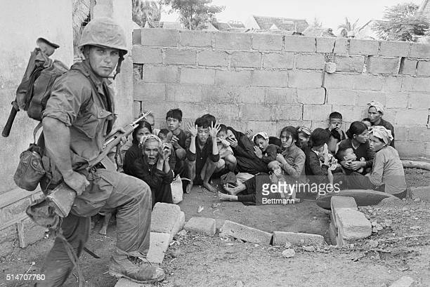 9/10/1965Qui Nhon South Vietnam Vietnamese women children and elders huddle together as US Marine Corporal Dave Taylor of State College Pennsylvania...