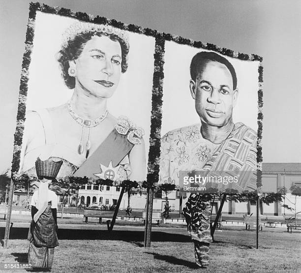 9/11/1961Accra Ghana Two Ghanaian women one carrying a child on her back looking at huge pictures of Queen Elizabeth II and President Nkrumah erected...