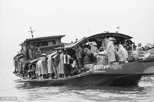 Amidst heavy torrential rains Vietnamese refugees huddle on their motorized junk 9/11 in Hong Kong Harbor awaiting investigation by the authorities...