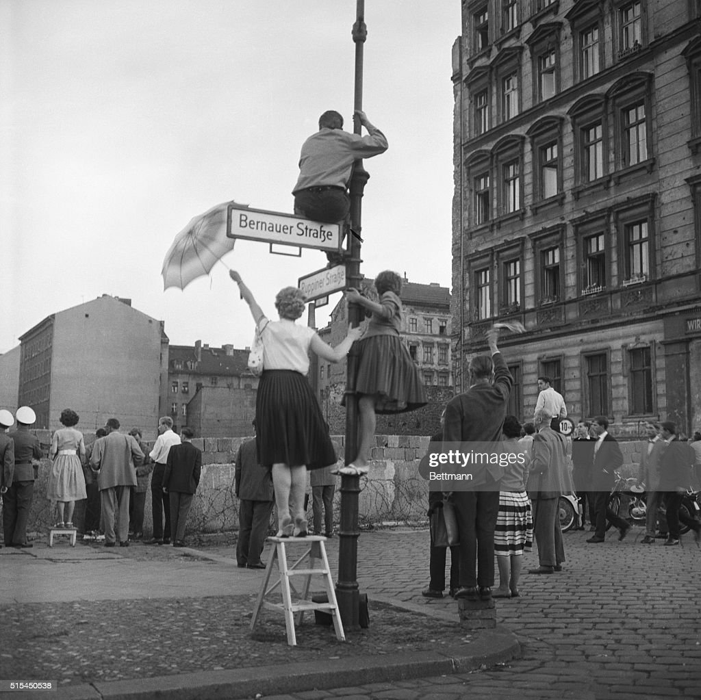 Berliners On Lampost/Ladder & Berlin Wal : News Photo